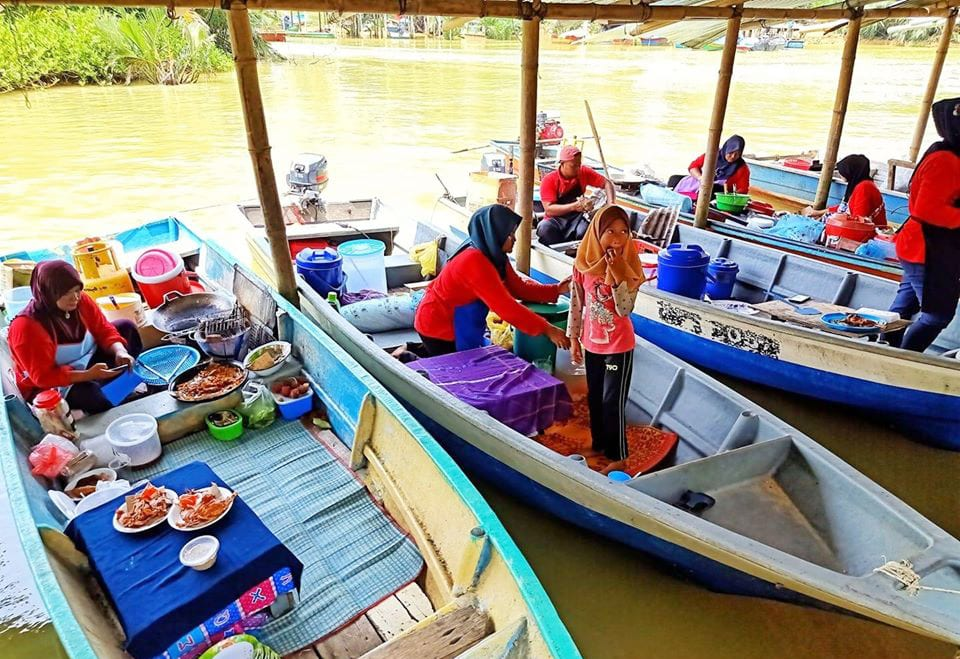 Boat traders selling local foods on a sampan at Suri Island Floating Market (Pasar Terapung Pulau Suri)